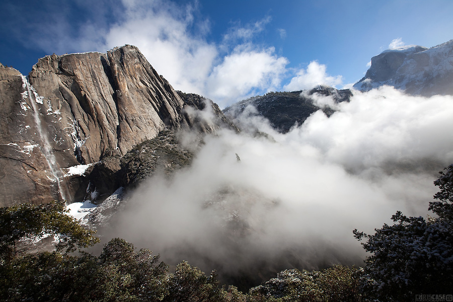 Fog rises from the Yosemite valley to reveal the iconic Half Dome and Yosemite Falls, Yosemite National Park, California.