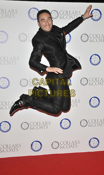 Vincent Simone.The Collars & Coats Gala Ball 2011, Battersea Evolution, Battersea Park, London, England..November 11th, 2011.full length black suit side smiling jump jumping in air gesture .CAP/CAN.©Can Nguyen/Capital Pictures.