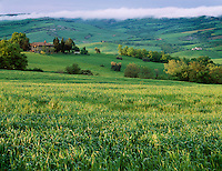 Tuscany, Italy      <br /> View of the rolling hills and valley of Val d'Orcia near under a bank of clouds near the hilltown of Contignano