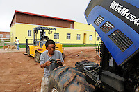 ANGOLA Malanje Black Stone Farm, a 20.000 hectare farm of chinese company CITIC construction corporation and angolian agency Gesterra which promotes large scale farms in Angola, projects of CITIC are financed by CIF China International Fund, Angola is paying back funds with crude oil, repair of chinese tractor, behind canteen and dogs, todays lunch dog meat with corn sweet and sour/ ANGOLA Malanje Black Stone Farm, eine 20.000 Hektar grosse Farm der chinesischen Firma CITIC construction corporation und der angolanischen Agentur Gesterra, die den Ausbau von Grossfarmen in Angola foerdert, Reparatur eines chinesisches Traktor, im Hintergrund Kantine und Hunde Meute, heute zum Mittag: Hundefleisch mit Mais suess sauer