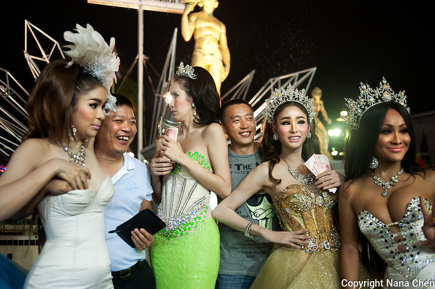 """A group of katoeys or """"ladyboys"""" pose with two Chinese tourists at the entrance of Tiffany's Show, a major tourist attraction for its cabaret style performances in Pattaya, one of the visited cities by Chinese tourists."""