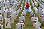 Memorial Day Ceremony at cemetary with American Flags with man walking through grave sites marked with flags