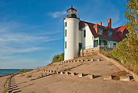 The Point Betsie Lighthouse in a fresh coat of white paint stands out again a blue sky like the beacon it is standing out on the shore guiding mariners away frm the point it sits on.  Lake Michigan shore, Benzie County, Michigan