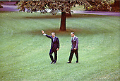 Washington, D.C. - August 17, 1973 -- United States President Richard M. Nixon waves to a photographer as he and his Chief of Staff, General Alexander M. Haig, Jr., walk alone on the White House grounds in Washington, D.C. on August 17, 1973..Credit: White House via CNP