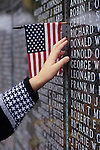Washington State Vietnam Veterans Memorial with names of the dead engraved in marble with American flags, and young girl (7 yrs old) reaching out at name on memorial, State Capital, Olympia, Washington USA   MR