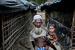 An elderly Rohingya Muslim man carries his grandson as they walk in an alley at a camp for Rohingya people.