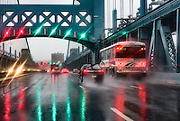 Hazardous driving conditions on a busy bridge during a heavy rain storm.