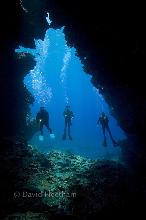 Three divers(MR) with lights, pictured at a cavern enterance.  Hawaii.