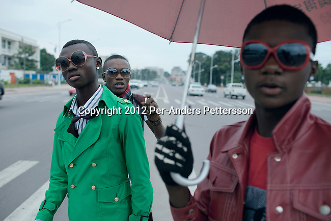 "KINSHASA, DEMOCRATIC REPUBLIC OF CONGO - FEBRUARY 10: Young Sapeurs show their designer label clothes while parading on Boulevard 30 Juin, while paying their respect to Stervos Nyarcos, the founder of the kitendi religion, which means clothing in local language Lingala. Nyarcos was known as the leader of the Sape movement, at Gombe cemetery on February 10, 2012 in Kinshasa, DRC. The word Sapeur comes from SAPE, a French acronym for Société des Ambianceurs et Persons Élégants or Society of Revellers and Elegant People and it also means, to dress with elegance and style"". Most of the young Sapeurs are unemployed, poor and live in harsh conditions in Kinshasa,  a city of about 10 million people. For many of them being a Sapeur means they can escape their daily struggles and dress like fashionable Europeans. Many hustle to build up their expensive collections. Most Sapeurs could never afford to visit Paris, and usually relatives send or bring clothes back to Kinshasa. (Photo by Per-Anders Pettersson)"