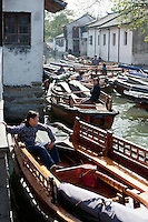 Villagers wait for people to hire their boats on a canal in Zhouzhuang Town of Jiangsu Province, China on November 18, 2008. Zhouzhuang, one of the most famous water townships in China, is noted for its profound cultural background, the well preserved ancient residential houses, the elegant watery views and the colourful local traditions and folklore. Sixty percent of the Zhouzhuang's structures were built during the Ming and Qing Dynasties from 1368 to 1911.