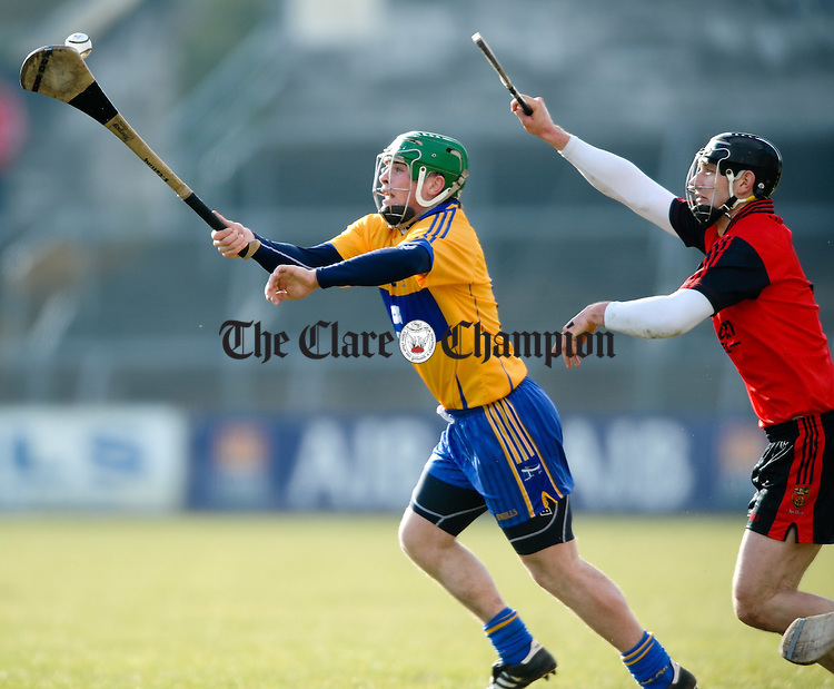 Clare's Sean Collins balances the ball ahead of Down's Kevin Mc Garry during their Division 2 National League game at Cusack park. Photograph  by John Kelly.