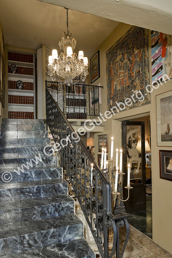 Stairway with crystal light fixture leads to Liberace library