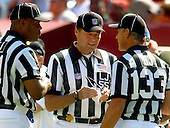 Landover, MD - October 2, 2005 -- Line judge Tom Barnes (55), center, cleans his glasses as he huddles with field judge Boris Cheek (41), left, and back judge Steve Freeman (133), right, during a break in the action at FedEx Field in Landover, MD where the Seattle Seahawks played the Washington Redskins  on October 2, 2005.  The Redskins won the game in overtime 20 - 17..Credit: Ron Sachs / CNP