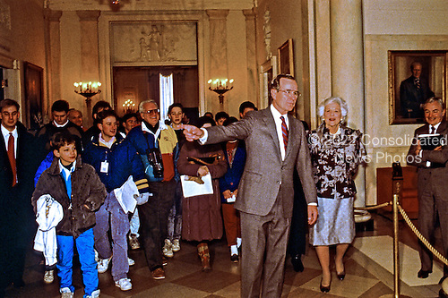 United States President George H.W. Bush conducts a visitors tour in the Grand Foyer of the White House in Washington, D.C. during his first full day as President on January 21, 1989.  First lady Barbara Bush accompanies at right.<br /> Credit: Dennis Brack / Pool via CNP