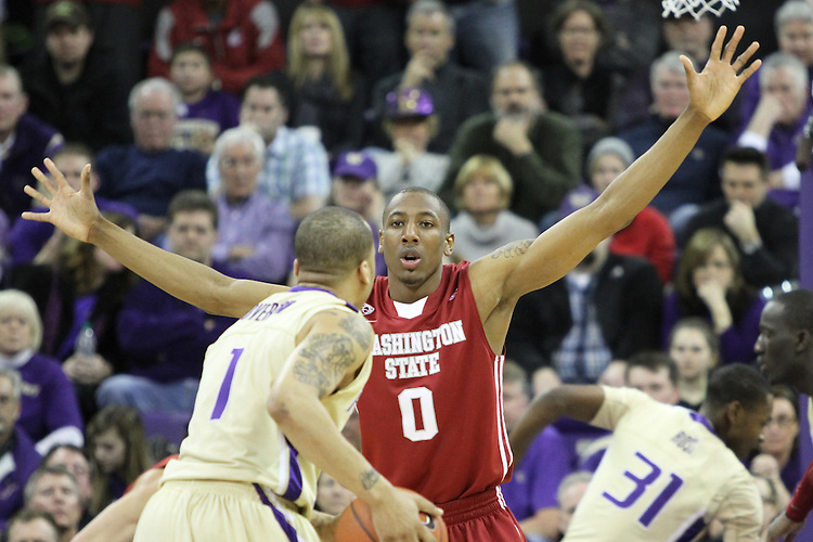 Marcus Capers (#0), Washington State junior guard, shows off his length in playing tough defense on Venoy Overton (#1) during the Cougars 80-69 road victory over arch-rival Washington at the Alaska Airlines Arena in Seattle, Washington, on February 27, 2011.  With the victory, Thompson and the Cougars swept the regular season series from the Huskies, two games to none.