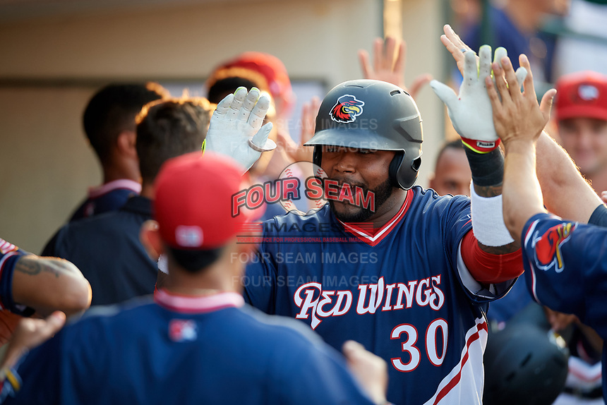 Rochester Red Wings designated hitter Kennys Vargas (30) high fives with his teammates in the dugout after hitting a home run in the bottom of the fourth inning during a game against the Pawtucket Red Sox on July 4, 2018 at Frontier Field in Rochester, New York.  Pawtucket defeated Rochester 6-5.  (Mike Janes/Four Seam Images)