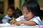 "In the capital of the Philippines, a girl who lives in the Manila North Cemetery enjoys drawing in class at the nearby Santa Mesa Heights United Methodist Church. Hundreds of poor families live in the cemetery, inside and between the tombs and mausoleums of the city's wealthy. They are often discriminated against, and many of their children don't go to school because they're too hungry to study and they're often called ""vampires"" by their classmates. With support from United Methodist Women, KKFI provides classroom education and meals to kids from the cemetery at this church."