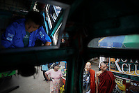 "Buddhist monks are seen through the window as Khin Aung, the driver of legendary ""Bayboo"" bus stops to pick-up passengers in central Yangon September 23, 2012. On the line 61, several ÒBaybooÓ buses take passengers from the North Dagon Township to the city. Possibly the oldest operating bus in the world, ÒBaybooÓ (big belly in Burmese language) is an improvised legend that maneuvers dirty roads for over 70 years. The original vehicle, of which only charm of its spectacular ugliness.is still visible, was WWII military Chevrolet C15. Modified to serve.public transportation, these ancient vehicles that would be banned by.law in almost any other country are great proof what MyanmarÕs.transportation is today.    REUTERS/Damir Sagolj (MYANMAR)"