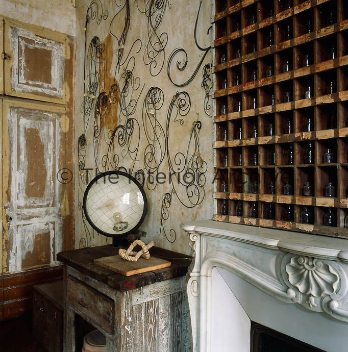 A corner of a period room with distressed finish on the walls. A collection of small glass bottles are displayed in a wooden rack resting on the mantelpiece of a marble fireplace. A vintage lamp stands on a rustic table in the corner.
