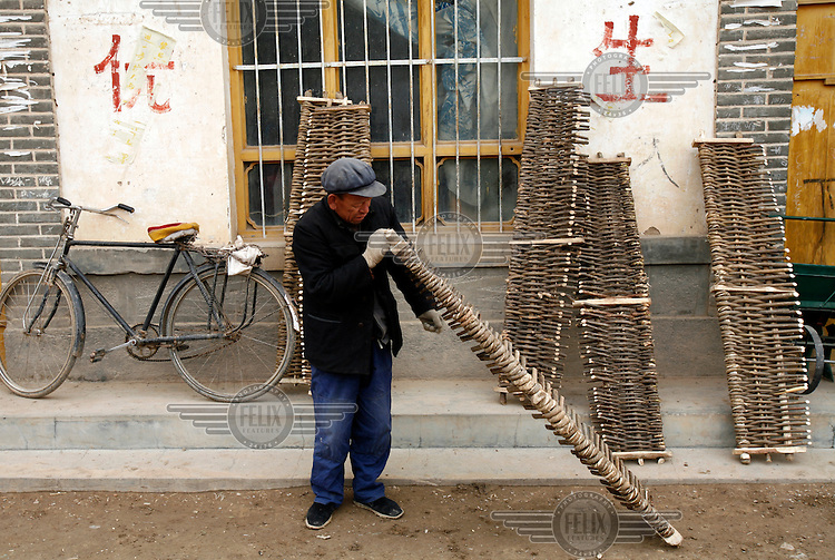 An elderly man at a local market inspects a farming tool used to smooth plowed earth.