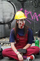Female participant in the Zombi Walk in Prague Europe in May 2014. Sitting on the ground wearing red overalls, a yellow helmet with nails hammered into it, and a hammer in her hand.