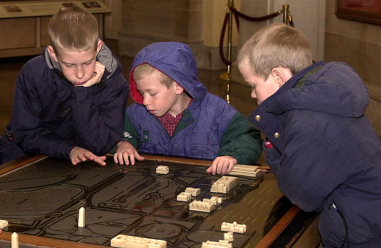 tourist3/010203 - Joel Nisbett (L), 11, Joe Nisbett (C), 9, and John Nisbett, 7, brothers visiting from Missouri, look at a map of Washington, D.C., in the crypt of the Capitol.