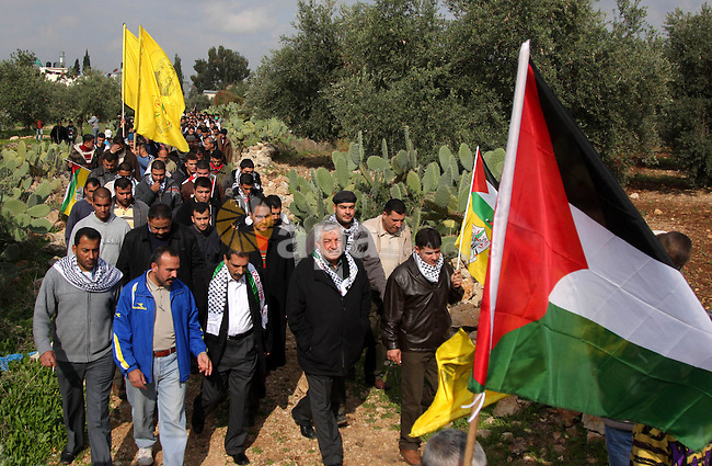 Palestinian demonstrators carrying the Palestinian flags during a protest against Israel's controversial separation barrier in the West Bank village of Nilin, near the city of Ramallah, Friday, Jan. 1, 2010. Photo by Issam Rimawi