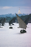 Against the almost unearthly backdrop of the Shwedagon Pagoda's golden stupa, fishing boats struggle up the Rangoon River under both sail and oars.