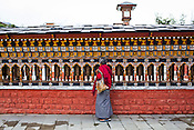 An old Bhutanese woman is seen turning the prayer wheels at the clock tower, the main square in Thimphu, Bhutan. Photo: Sanjit Das/Panos