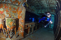 TR4555-D. scuba diver (model released) swims through kitchen inside USS Kittiwake shipwreck. This was a diver support vessel in the US Navy. Sunk deliberately in 2011 to make an artificial reef. Now one of the most popular dive sites on Grand Cayman Island. Cayman Islands, Caribbean Sea.<br /> Photo Copyright &copy; Brandon Cole. All rights reserved worldwide.  www.brandoncole.com
