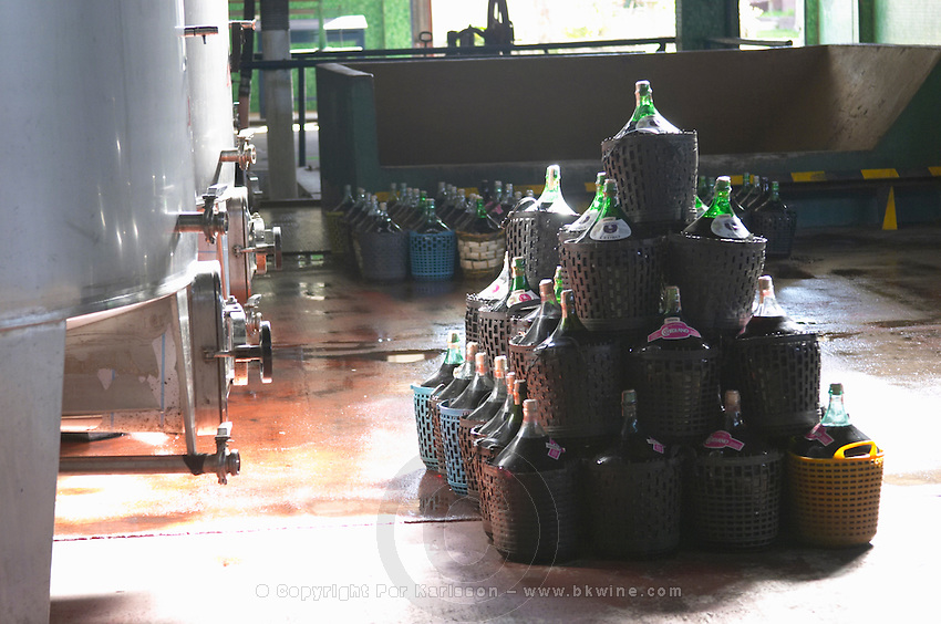 A pile of demijohns of the popular rosado wine sold locally in plastic baskets and some stainless steel fermentation tanks. Bodega Plaza Vidiella Winery, Las Brujas, Canelones, Uruguay, South America