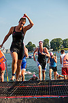 Triathlon swimmers run out of the water.