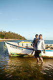 MAURITIUS, father and son stand in front of a fishing boat after a long day on the water, Bel Ombre, Indian Ocean