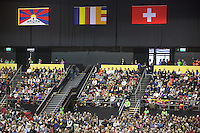 "Switzerland. Basel. St. Jakobshalle. A crowd of people listen to His Holiness the Dalai Lama during his public lecture on Bodhicitta. The topic of his talk is about Nagarjuna's Commentary on Bodhicitta which touches on two aspects of the awakening mind, the twin qualities of wisdom and compassion, which are necessary for anyone who aspires to be a better person and implement changes in their lives. The Tibetan flag, also known as the ""snow lion flag"" and the 'Free Tibet flag', was a flag of the military of Tibet, introduced by the 13th Dalai Lama in 1912 and used for the same capacity until 1959. Designed with the help of a Japanese priest, it reflects the design motif of the Japanese military's Rising Sun Flag. Since the 1960s, it is used a symbol of the Tibetan independence movement. The flag of Switzerland consists of a red flag with a white cross (a bold, equilateral cross) in the centre. 7.02.2015 © 2015 Didier Ruef"