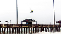 Kite Boarder Dimitri Maramenides gets some big air next to Jennette's Pier in Nags Head, N.C., as Hurricane Florence makes landfall further south on Friday, Sept, 14, 2018.   (L. Todd Spencer/The Virginian-Pilot via AP)