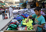 A Syrian boy sells clothes in a market in a rebel-controlled area in the northern Syrian city of Aleppo, on August 31, 2015. Photo by Ameer al-Halbi