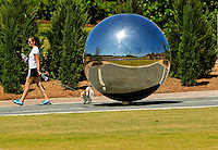 "Photography of Charlotte NC's Midtown Park on the Little Sugar Creek Greenway, a public park with more than 19 miles of trails and land connectors. Charlotte designed the Sugar Creek Greenway with the goal of connecting neighborhoods, landmarks and activities and increasing the Queen City's pedestrian-oriented activities. The greenway provides environmental benefits such as improved water quality through stream buffering, wildlife habitats and flood control. Photo shows the ""Sight Unseen"" artwork by Po Shu Wang and Louise Bertelsen at Midtown Park. The gleaming sphere, installed in April 2012, is designed to bring enjoyment of visual art to the sight-impared. The artists blended Braille embossed dots with modified music box readers to create the multi-dimensional pieces, described by the artists as Braille music boxes."