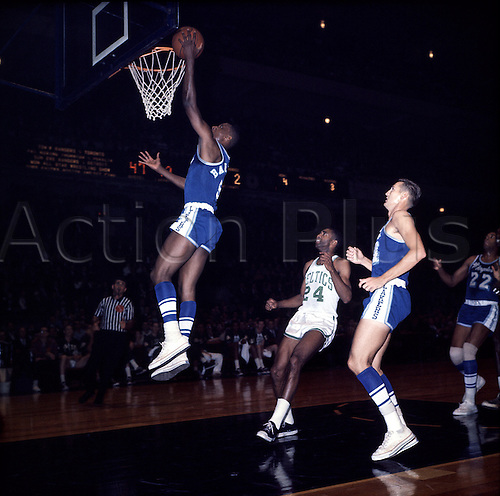 1960's:  Elgin Baylor, left, of the Los Angeles Lakers with a layup during a Lakers game versus the Boston Celtics at the Boston Garden in Boston, Massachusetts.  Jerry West of the Lakers, right, looks on..