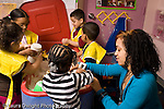 Education Preschool 3-4 year olds female student teacher working with girl at sand table group playing in background horizontal