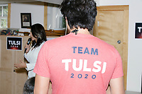 """Campaign staff wear """"Team Tulsi 2020"""" shirts as Democratic presidential candidate and Hawaii representative (D-HI 2nd) Tulsi Gabbard speaks at a campaign event at Weare Public Library in Weare, New Hampshire, on Thu., September 5, 2019."""
