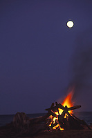 Bonfire at night with moonrise, Kealia Beach, east Kauai.