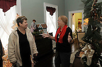 STAFF PHOTO FLIP PUTTHOFF <br /> PEEL MANSION CHRISTMAS<br /> Mary Jenkins, left, hears Judy Grant, a docent at the Peel Mansion, talk about the history of the historic home while Jenkins toured the mansion during the Christmas open house at The Peel Mansion and Heritage Gardens in Bentonville. Visitors toured rooms of the historic home that were decorated in various themes while docents in period clothing revealed the mansion's history. The open house was the last opportunity for visitors to see the Peel Mansion decorated for Christmas.