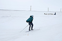 Anjanette Steer, skiing on the Bering Sea as Blake Freking approaches Nome during the 2010 Iditarod