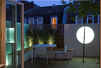 Dusk view out onto the tiny decked terrace with moveable box benches that act as storage. Round light feature provides focus