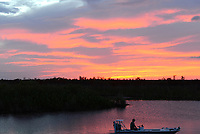Florida sunsets can be beautiful with many different colors. Additionally, we see a fisherman returning to the boat ramp; did he catch anything? I do not know !