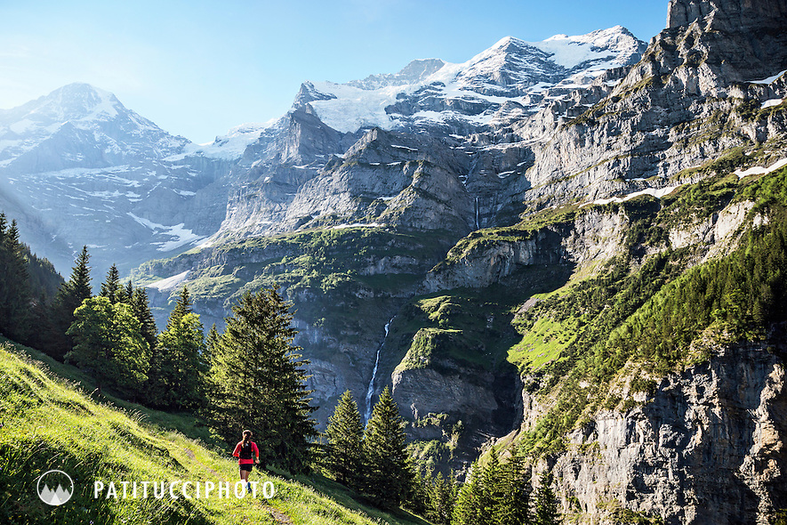 Woman trail running on singletrack above Lauterbrunnen Valley with views of the Jungfrau and Mönch in the Berner Oberland, Switzerland