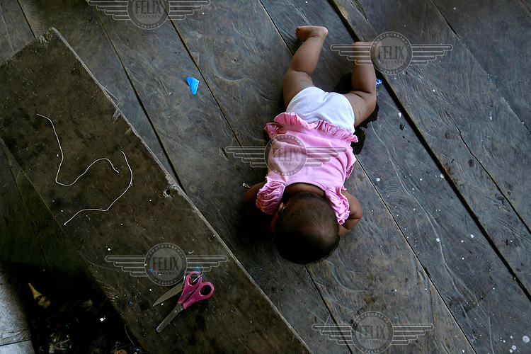 A baby girl crawls in one of the homes in the Quichua community of San Pedro Sumino.