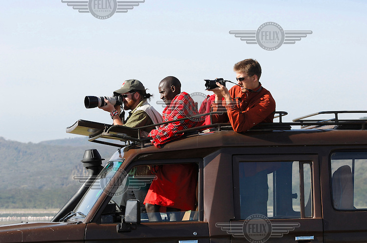 Tourists, standing beside their Maasai guide, photograph the wildlife from the roof of their jeep....