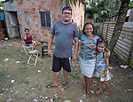 Members of an indigenous family pose in front of their house in the Nacoes Indigenas neighborhood in Manaus, Brazil. The neighborhood is home to members of more than a dozen indigenous groups, many of whose members have migrated to the city in recent years from their homes in the Amazon forest.