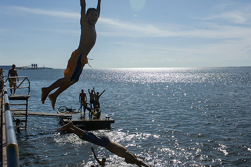 Santarem, Brazil. Boys playing in the river, diving from a wooden walkway and pontoon with the Cargill soya port in the distance.